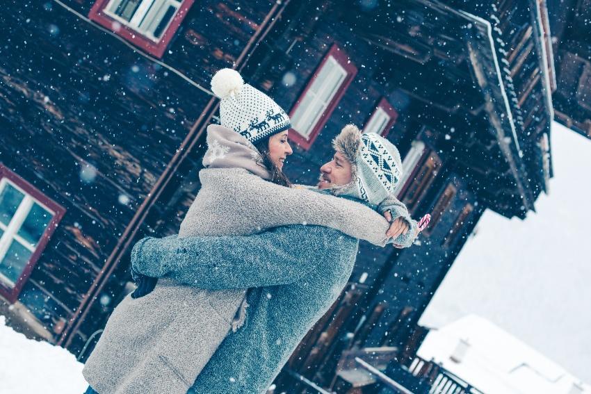 Paar im Winter vor einer Berghütte