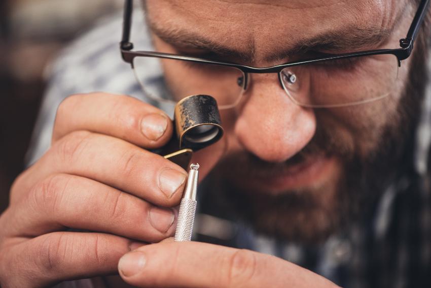 Ein Goldschmied betrachtet einen Diamanten durch eine Lupe 4Cs der Diamanten