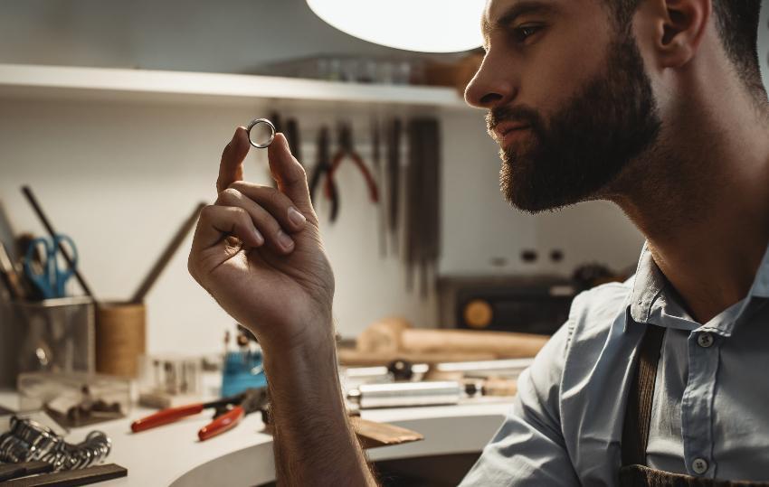 Ein Goldschmied betrachtet in seiner Werkstatt nach getaner Arbeit einen fertigen Ring Ringschiene anpassen