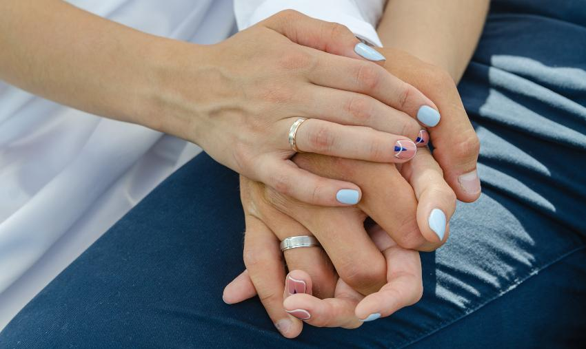 Ein Paar hält sich bei den Händen, an den Ringfingern tragen beide einen passgenauen Ring Ringschiene anpassen