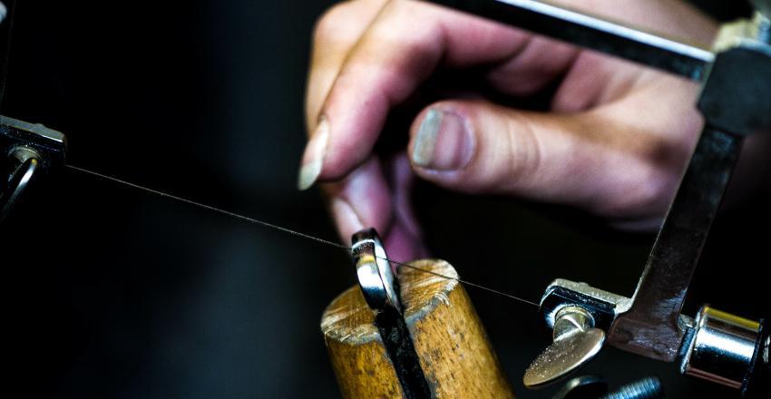 Eine Goldschmiedin ist dabei einen Ring mit einer Säge aufzuschneiden, um die Größe anzupassen Ringschiene anpassen