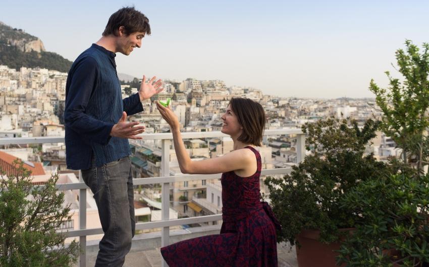 Frau kniet und macht Mann einen Heiratsantrag - Verlobungsring für den Mann