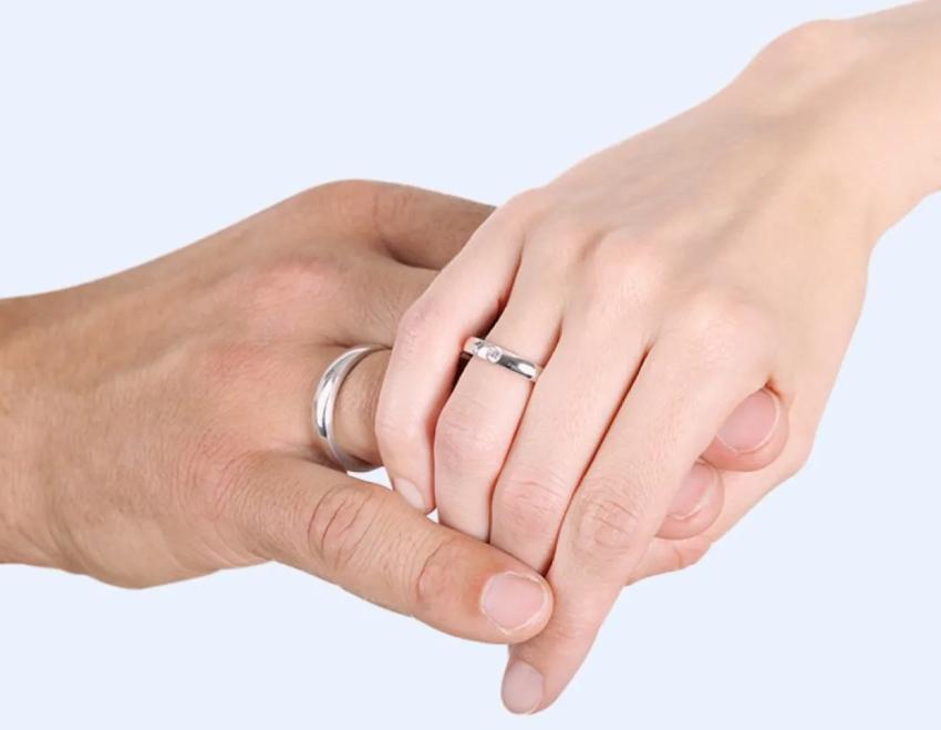 Hände eines Paares in der Nahaufnahme mit Eheringen