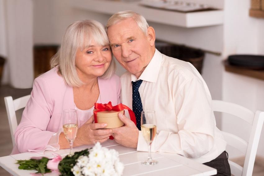 Älteres Ehepaar mit Geschenkbox sitzt am Tisch