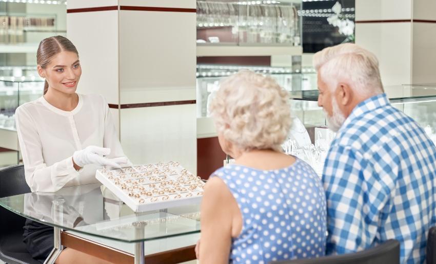 Altes Ehepaar sucht sich beim Juwelier Ringe aus