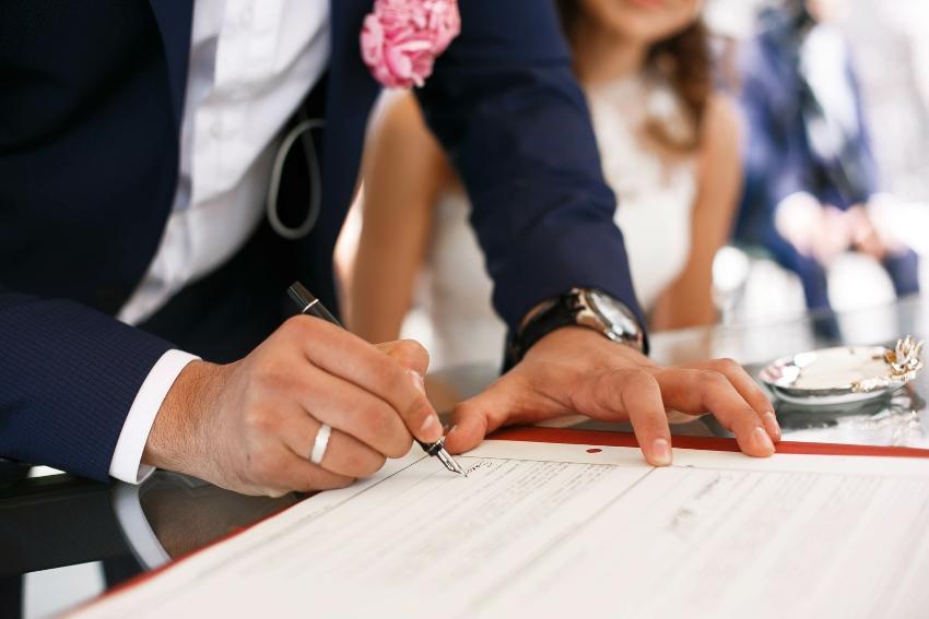 Bräutigam unterschreibt Heiratsurkunde
