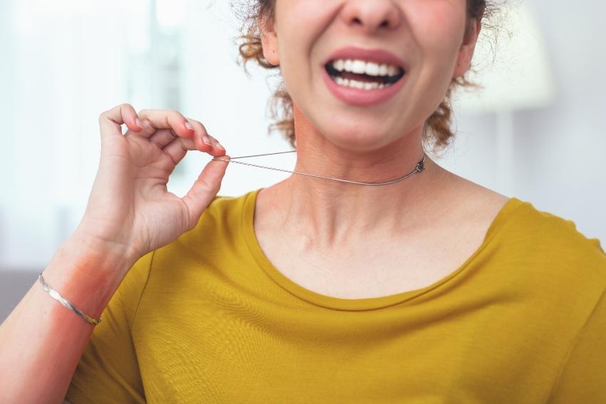 Frau mit Halskette hat allergische Reaktion - Schmuck und Ringe für Metallallergiker