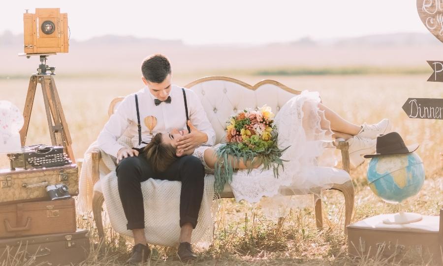 Junges Brautpaar sitzt im Feld auf einer Couch - Bohemian-Hochzeit