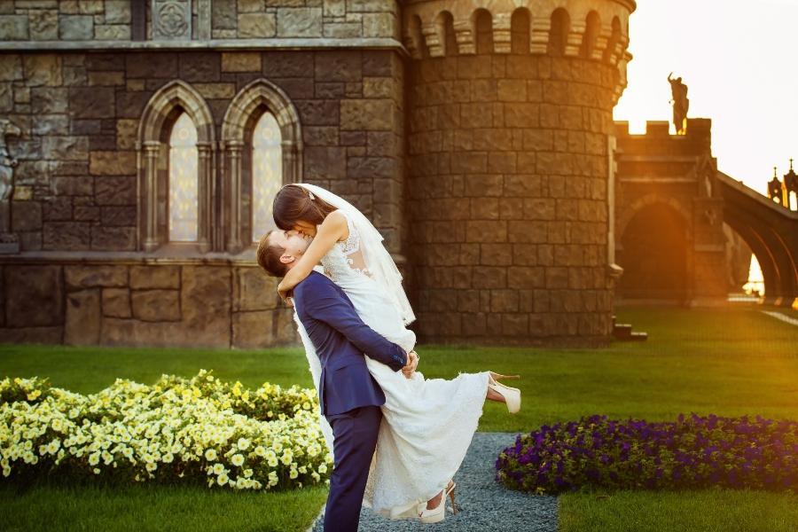 Junges Brautpaar umarmt sich vor Burg/Schloss - Mittelalter-Hochzeit