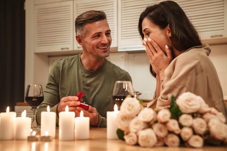 Junges Paar bei Kerzen und Rosen - er macht einen Heiratsantrag - Ideen für den Heiratsantrag