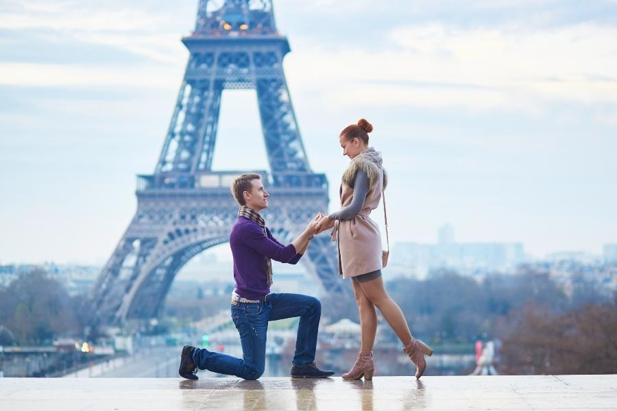 Junger Mann macht Freundin vor dem Eiffelturm einen Hochzeitsantrag - Ideen für den Heiratsantrag