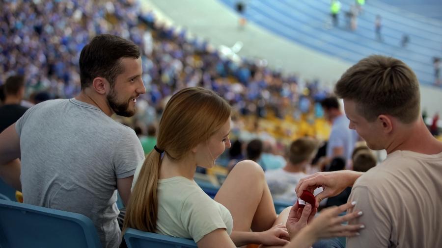 Junger Mann macht Freundin Hochzeitsantrag in einem Stadion