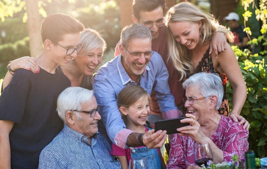Großfamilie schaut auf Smartphone - die Platinhochzeit