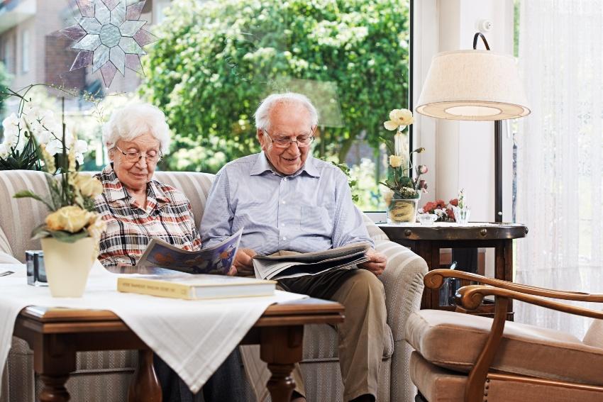 Altes Ehepaar sitzt auf der Couch und liest Zeitung - Die Platinhochzeit