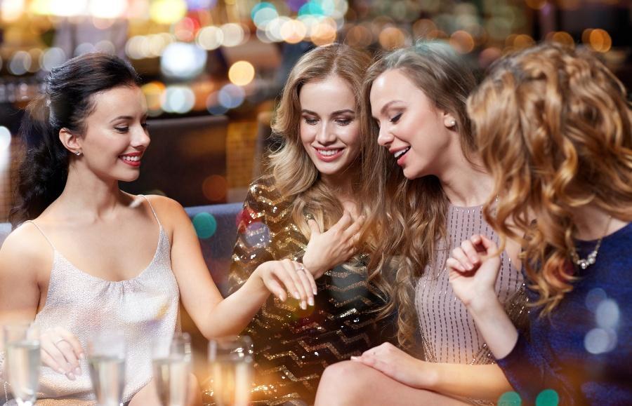 Junge Frau zeigt Freundinnen ihren Verlobungsring