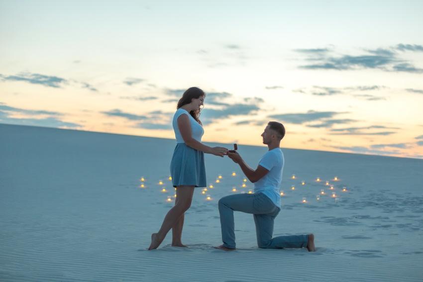 Junge Mann macht Frau am Strand einen Hochzeitsantrag