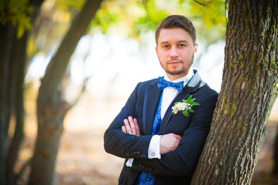 Junger Bräutigam lehnt lässig an Baum - nachhaltige Hochzeit