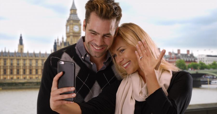 Junges Paar - Frau zeigt Verlobungsring in die Handy-Kamera - Heiratsantrag in London