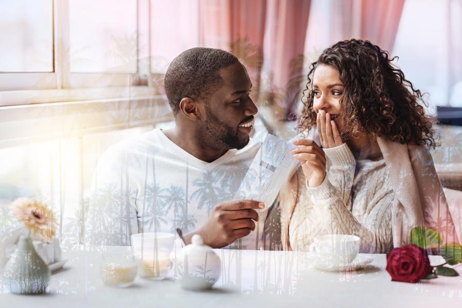Junger Mann überreicht seiner Partnerin Flugticktes, vielleicht für einen Heiratsantrag in London